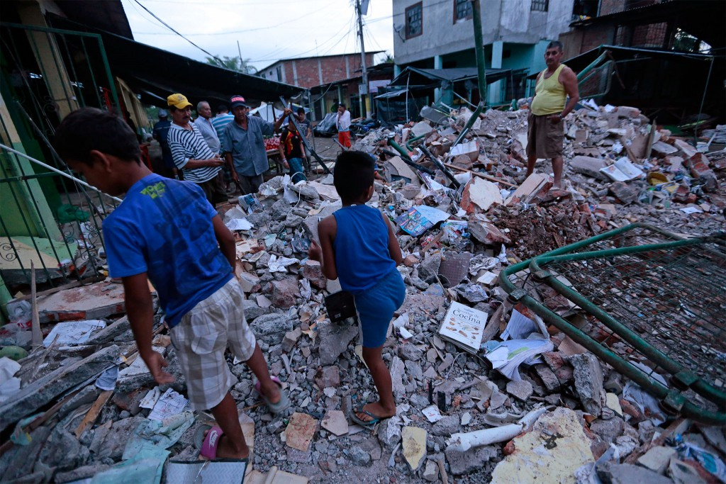 People stand amongst the rubble of fallen homes in Manta on April 17, 2016, after a powerful 7.8-magnitude earthquake struck Ecuador on April 16. At least 77 people were killed when a powerful 7.8-magnitude earthquake struck Ecuador, destroying buildings and a bridge and sending terrified residents scrambling from their homes, authorities in the Latin American country said on April 17. / AFP / JUAN CEVALLOS (Photo credit should read JUAN CEVALLOS/AFP/Getty Images)